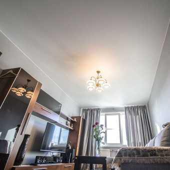 Матовый белый натяжной потолок с люстрой в гостиной