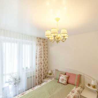 Сатиновый белый натяжной потолок в спальне